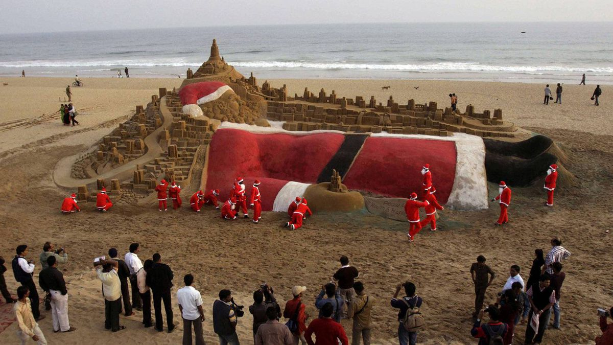Sand schulpture artists dressed as Santa Claus create a Santa Claus sculpture on Christmas Eve on Puri Golden Beach in India,