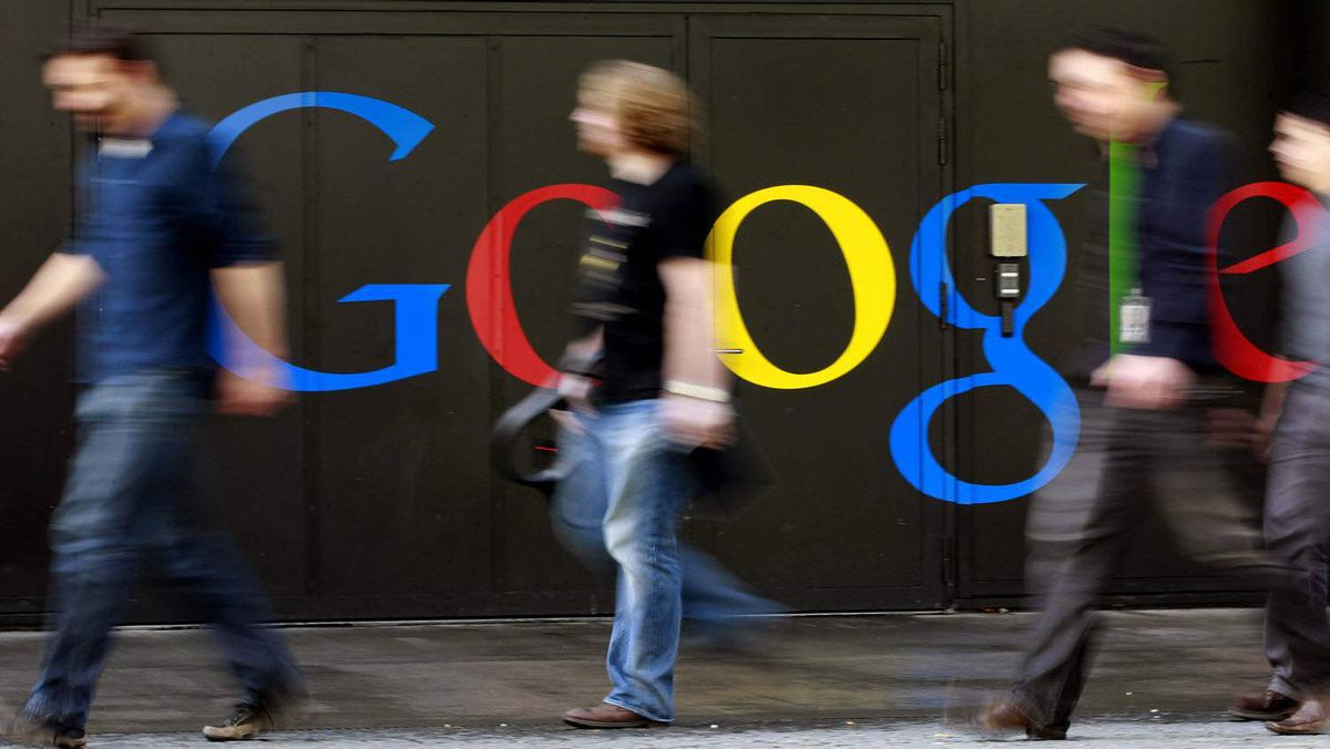 People walk past a logo next to the main entrance of the Google building in Zurich March 9, 2011.