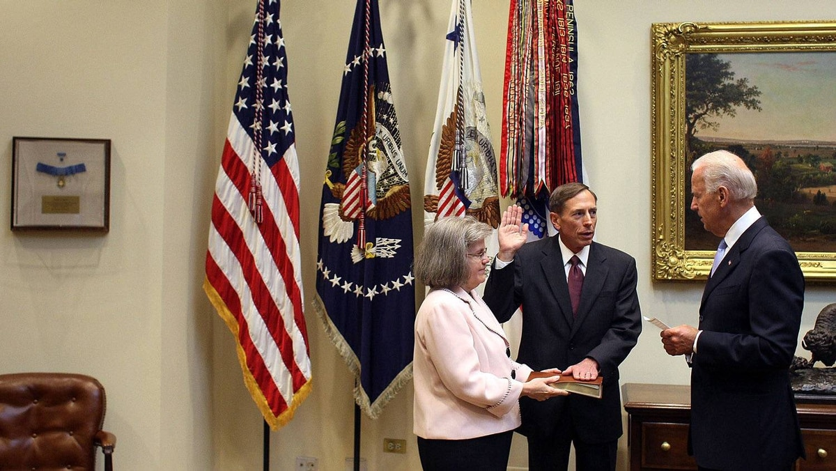 Vice President Joseph Biden (R) swears in David Petraeus (C) to be Director of the Central Intelligence Agency, while his wife Holly Petraeus holds a Bible, in the Roosevelt Room at the White House, on September 6, 2011 in Washington, DC.
