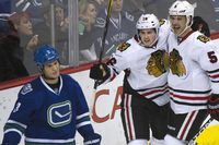 Chicago Blackhawks' Steve Montador (R) and Marcus Kruger celebrate after their team mate Andrew Brunette (not seen) scored against the Vancouver Canucks during the second period of their NHL hockey game in Vancouver, British Columbia November 16, 2011. Canucks' Kevin Bieksa is seen at left.