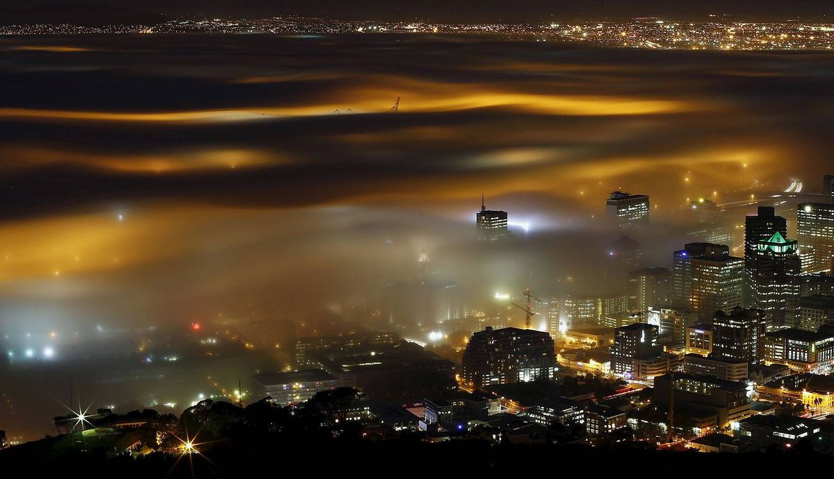Seasonal fog is illuminated by the lights of Cape Town harbour as the city prepares for the start of the southern hemisphere winter