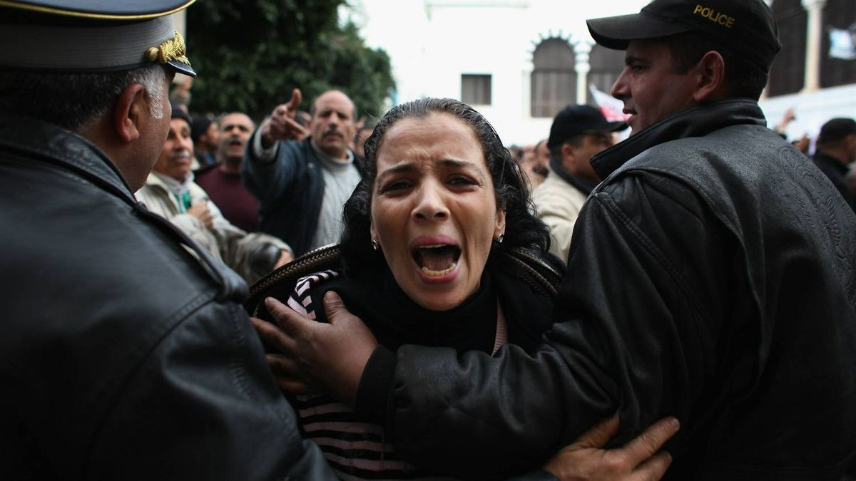 Police hold back protestors outside the Tunisian Prime Ministers office on January 22, 2011 in Tunis, Tunisia. Policemen joined the people of Tunis to protest about their working conditions and to distance themselves from ousted former president Zine al-Abidine Ben Ali. Many officers say they are also victims of the Ben Ali regime.