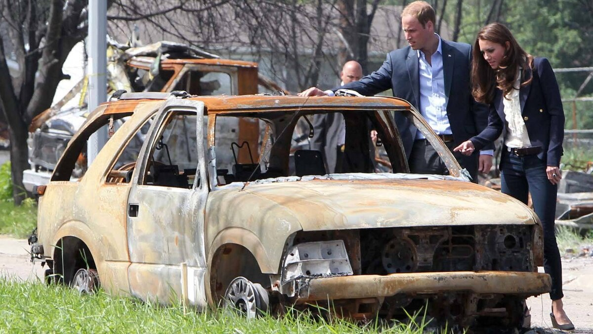 The Duke and Duchess of Cambridge look at a burned-out car in Slave Lake, Alta., on Wednesday, July 6, 2011. THE CANADIAN PRESS/Jonathan Hayward