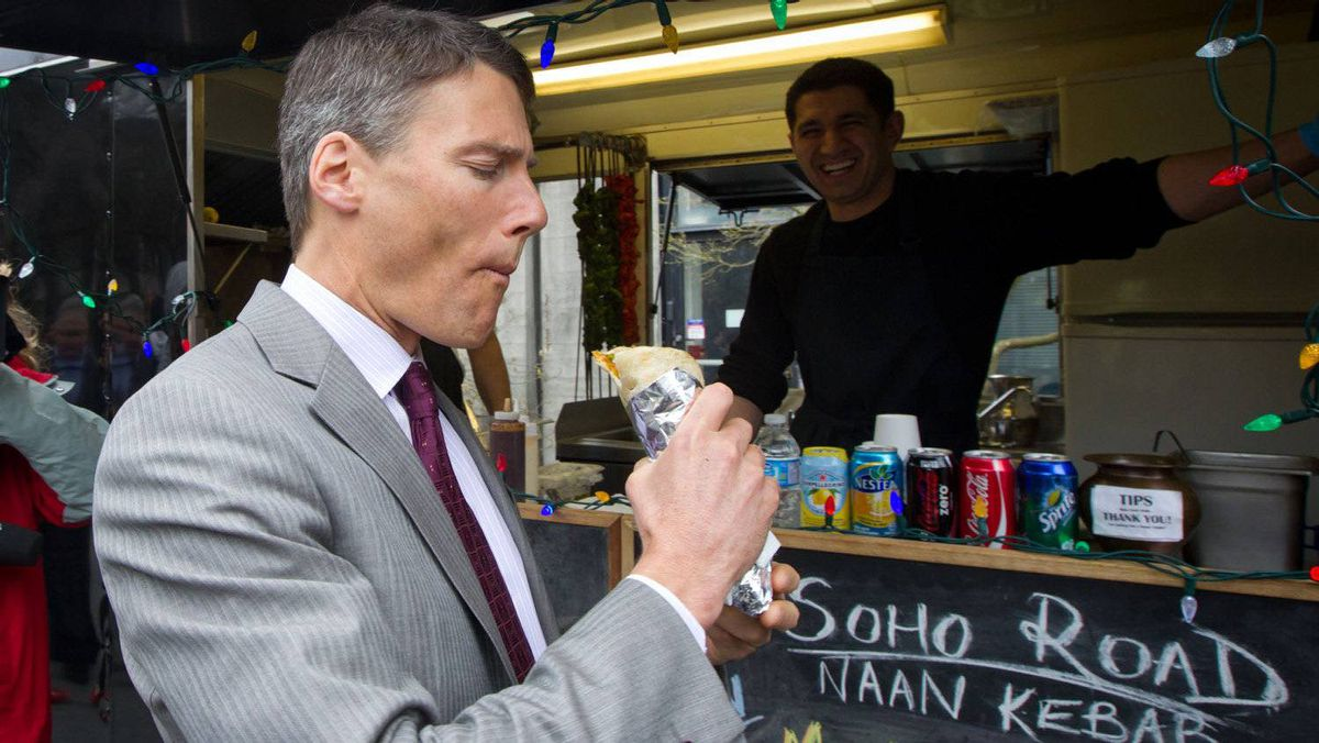Vancouver Mayor Gregor Robertson takes a bite of a vegetarian naan wrap prepared by Sarb Mund at his Soho Road food truck outside Vancouver City Hall.