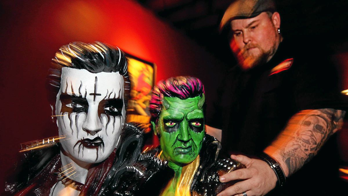 """Artist Gary Pullin and two Elvis busts from the God Save the King exhibit, """"Black Metal King"""" by Paige Reynolds and """"Hellvis"""" by Gary Pullin"""
