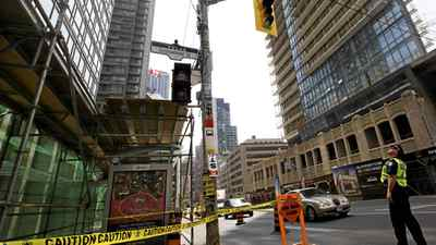 A police officer looks up where glass had fallen from a highrise in downtown Toronto at Bay and Grenville Streets injuring one person on Aug.15, 2011.