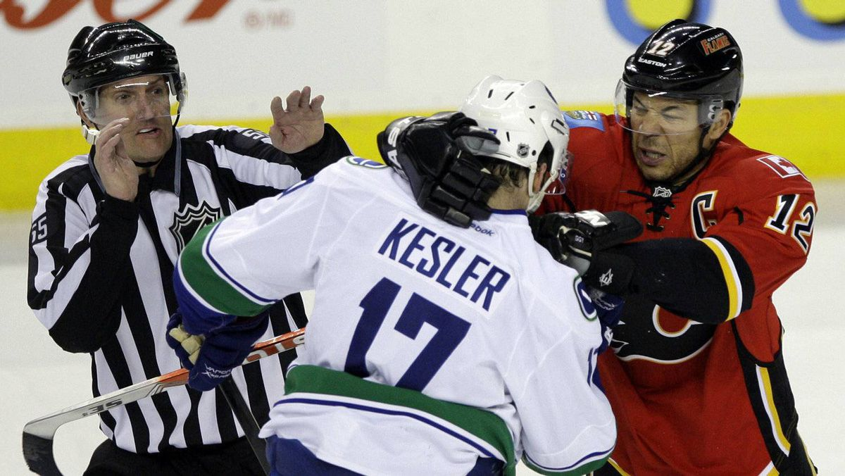Vancouver Canucks' Ryan Kesler (C) and Calgary Flames' Jarome Iginla mix it up during second period action as Linesmen Shane Heyer (L) tries to break them up in their NHL hockey game in Calgary, Alberta, April 5 , 2012.