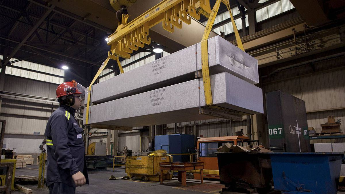 Employee supervising finished aluminium product at Rio Tinto Alcan casting centre.