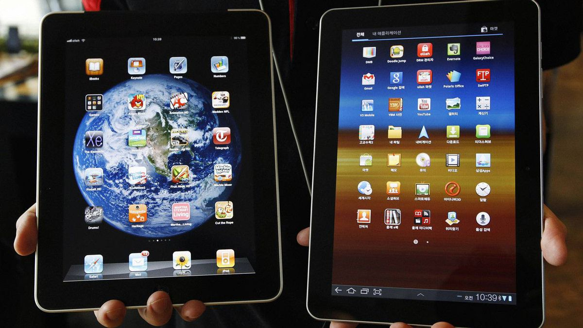 File picture shows an employee of South Korean mobile carrier KT holding a Samsung Electronics' Galaxy Tab 10.1 tablet (R) and Apple's iPad tablet in Seoul, Aug. 10, 2011.