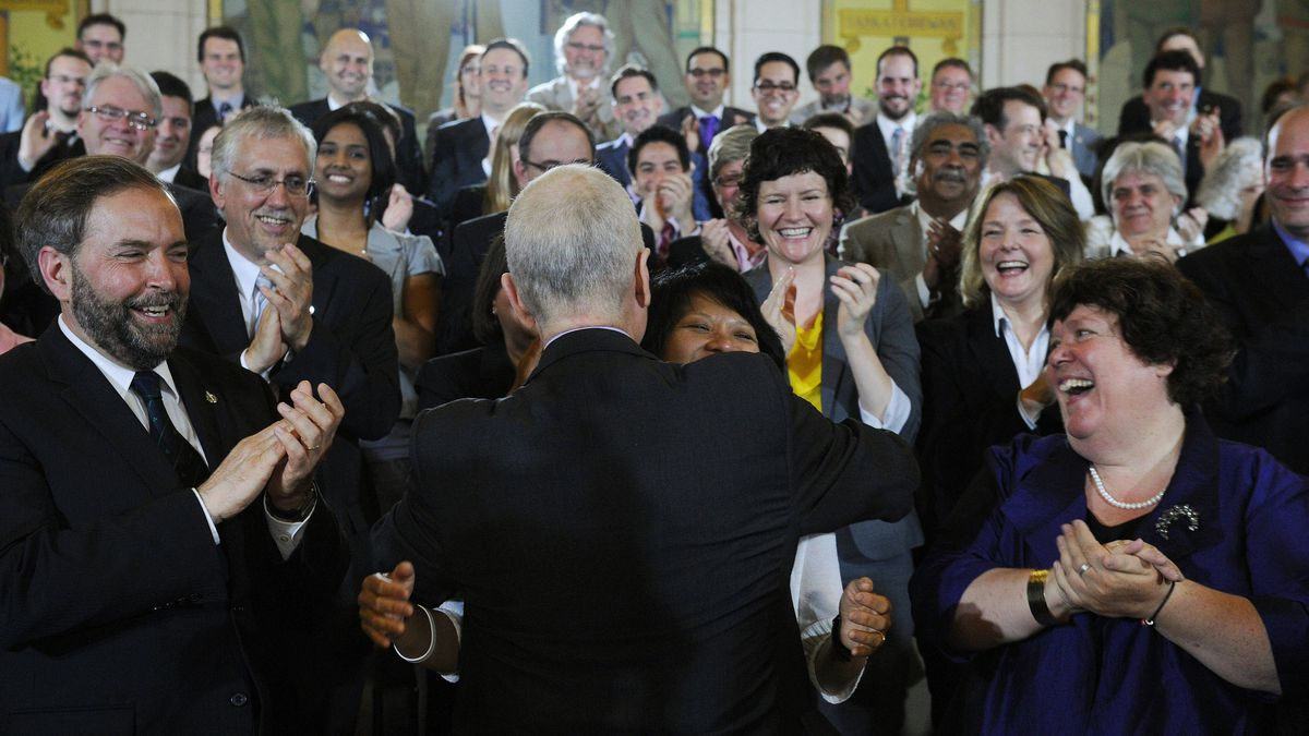 NDP Leader Jack Layton is hugged by his wife and MP Olivia Chow as he is applauded by his new caucus following a speech on Parliament Hill in Ottawa on May 24, 2011.