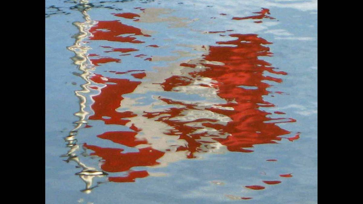 Taken with handheld camera on Granville Island, Vancouver of reflection of a flag in the water of False Creek, 2009.