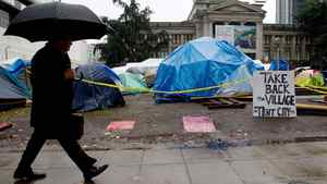 A businessman walks past the Occupy Vancouver site in downtown Vancouver on Monday Nov.7, 2011. City officials have notified the camp to immediately pack up their tents and vacate the site.