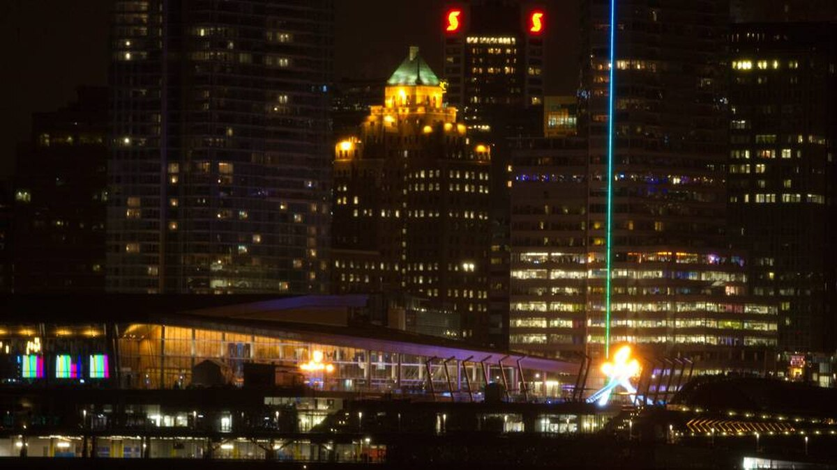 The city skyline is seen as the Olympic flame burns in a caldron along the waterfront at the 2010 Winter Olympic Games in Vancouver, Saturday, Feb. 27, 2010.
