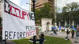 An unidentified man secures a banner in the Grand Parade in Halifax on Monday, Oct. 17, 2011 as the Occupy Nova Scotia corporate greed protest continues.