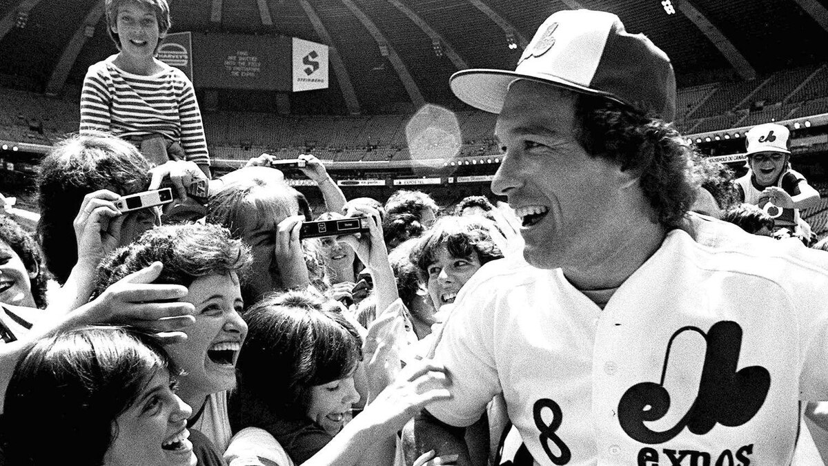 In this June 24, 1983 file photo, Montreal Expos catcher Gary Carter is mobbed by admiring fans at camera day prior to a baseball game against the Pittsburgh Pirates in Montreal.