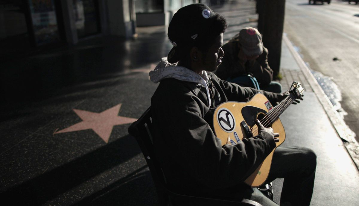 Josh Douglas, 19, (L) and Dawn Taylor, 22, sit on a bench on Hollywood Boulevard as the sun rises near the site of the 84th Academy Awards in Hollywood, California February 23, 2012.
