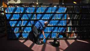 John Elmslie, a librarian at the The Toronto Reference Library shelves books after the library opened its' doors to the public for the first time in two weeks, on Friday March 30, 2012.