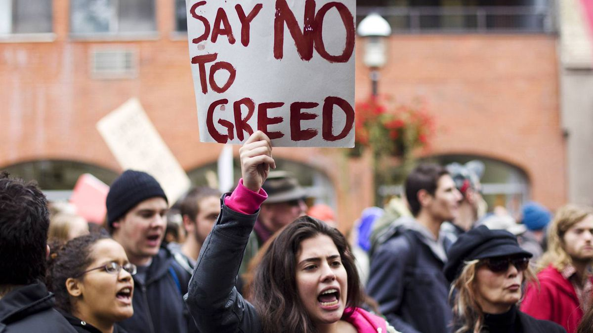 A protester displays a sign during an Occupy Toronto demonstration in Toronto on Saturday Oct. 15, 2011. Thousands of protesters gathered peacefully in Canadian cities, including Toronto and Montreal, joining the Occupy Wall Street demonstrations that began in New York and have spread worldwide.