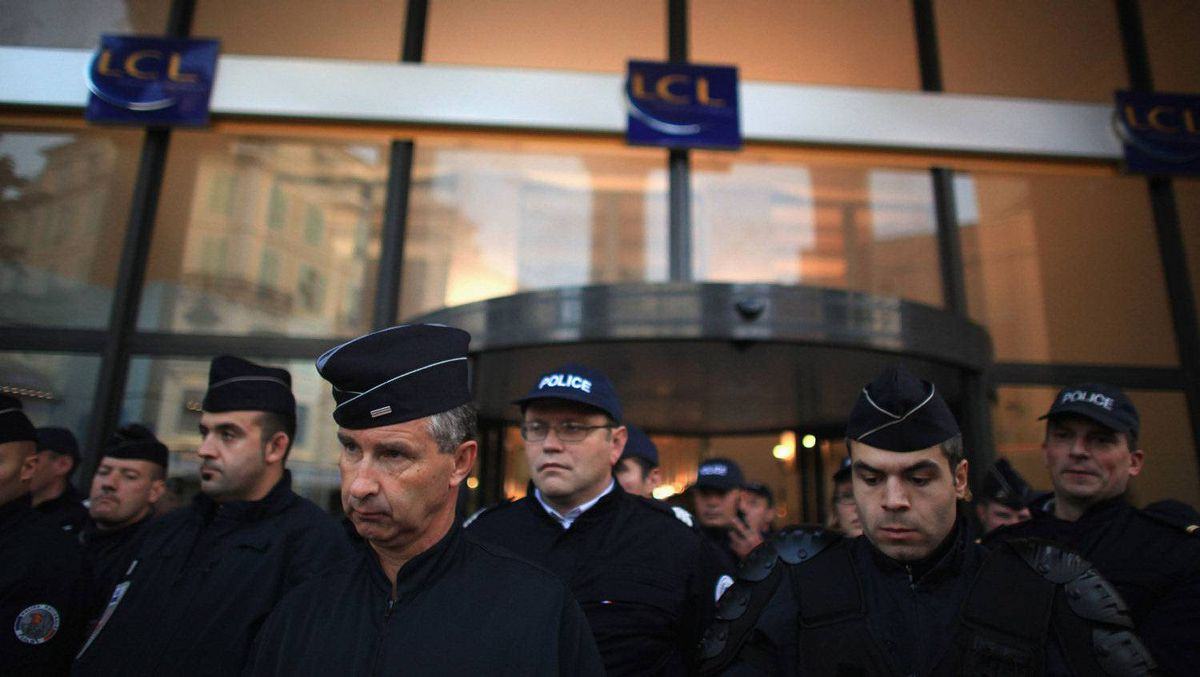 Police guard a bank as protesters demonstrate outside in the centre of Nice, Nov. 2, 2011. Anti-G20 demonstrators have gathered in Nice ahead of the arrival of the world's top economic leaders for the G20 summit in Cannes on Nov. 3 and 4. The leaders are expected to debate current issues surrounding the global financial system in the hope of fending off a global recession and finding an answer to the euro zone crisis. Christopher Furlong/Getty Images