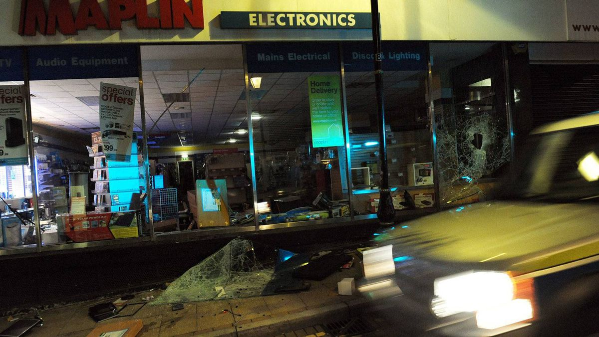 A police car passes an electrical shop that had been raided during a night of unrest in Birmingham, central England, on August 8, 2011.