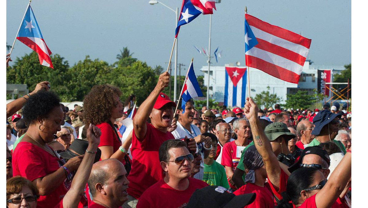 People wave flags of Cuba (blue stripes) and Puerto Rico (red stripes) during the celebrations for the 58th anniversary of the Moncada barrack attack, at Revolution Square in Ciego de Avila, in the Cuban province of the same name, on July 26, 2011.