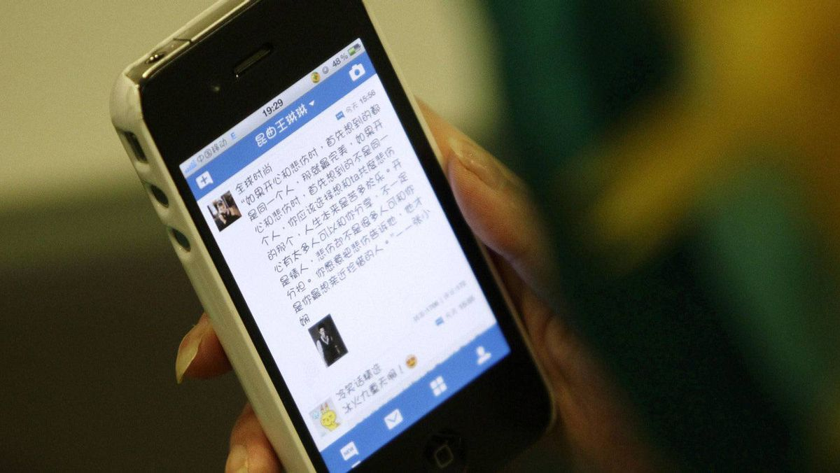 A woman loads a Chinese microblog website on her Apple iPhone in Beijing, September 16, 2011.