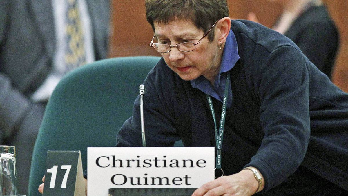 A worker makes adjusts the witness chair intended for Christiane Ouimet, the former integrity commissioner, at a Commons committee hearing in Ottawa on Feb. 8, 2011.