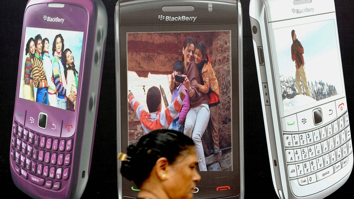 An Indian pedestrian walks past a billboard for Blackberry phones in Mumbai on August 13, 2010.