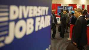 Attendees carry their resumes as they arrive at a job fair in a Washington hote in this file photo.
