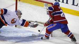 New York Islanders goalie Mikko Koskinen makes a diving save on Montreal Canadiens defenseman James Wisniewski during the second period of NHL hockey action in Montreal, February 10, 2011.