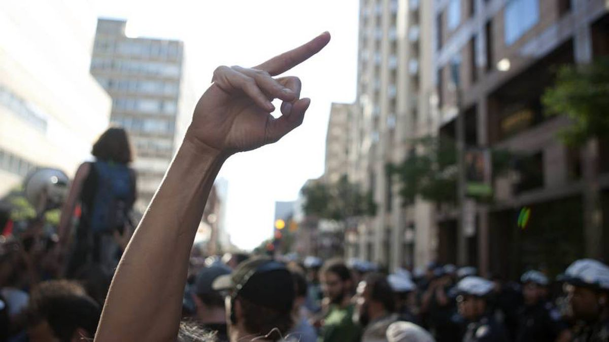 A woman gestures towards the ranks of police officers as a speaker addresses demonstrators gathered outside Toronto Police headquarters.