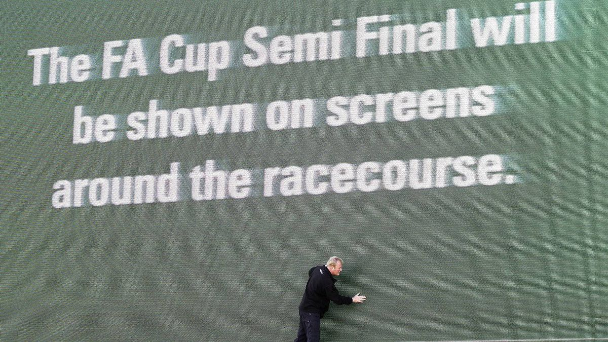 A worker checks a screen advertising the showing of the day's football match between Liverpool and Everton before the Grand National horse race at Aintree Racecourse Liverpool, England, Saturday, April 14, 2012. The Grand National is a world-famous National Hunt horse race which is held annually at Aintree Racecourse, near Liverpool, England. It is a handicap steeplechase run over a distance of 4 miles and 856 yards (7,242 m), with horses jumping thirty fences over two circuits of Aintree's National Course.(AP Photo/Jon Super)