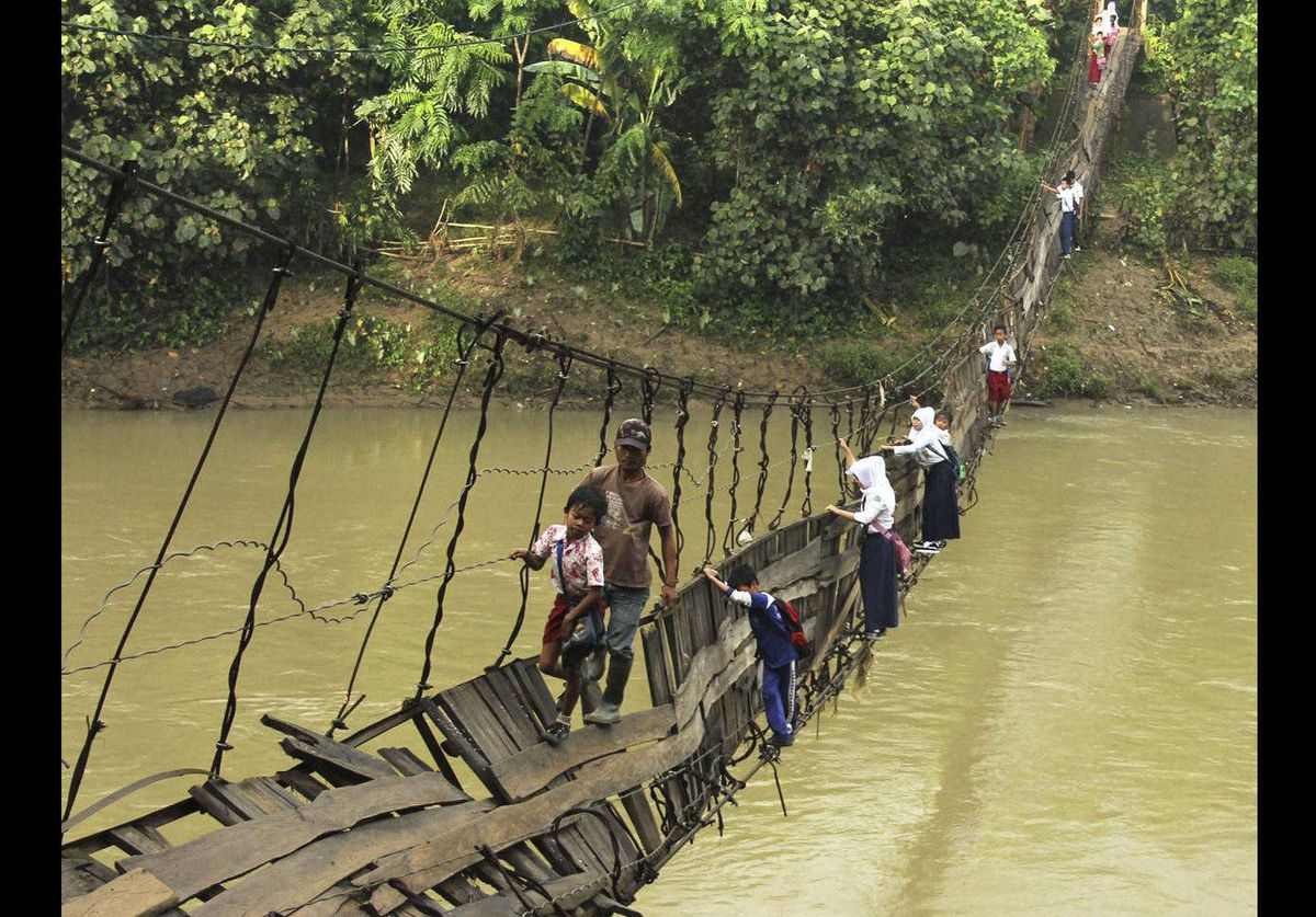 Students make their way across a damaged suspension bridge to go to their school on the other side of Ciberang river in Lebak, Banten province, Indonesia. The bridge was badly damaged after it was hit by a flood last week.