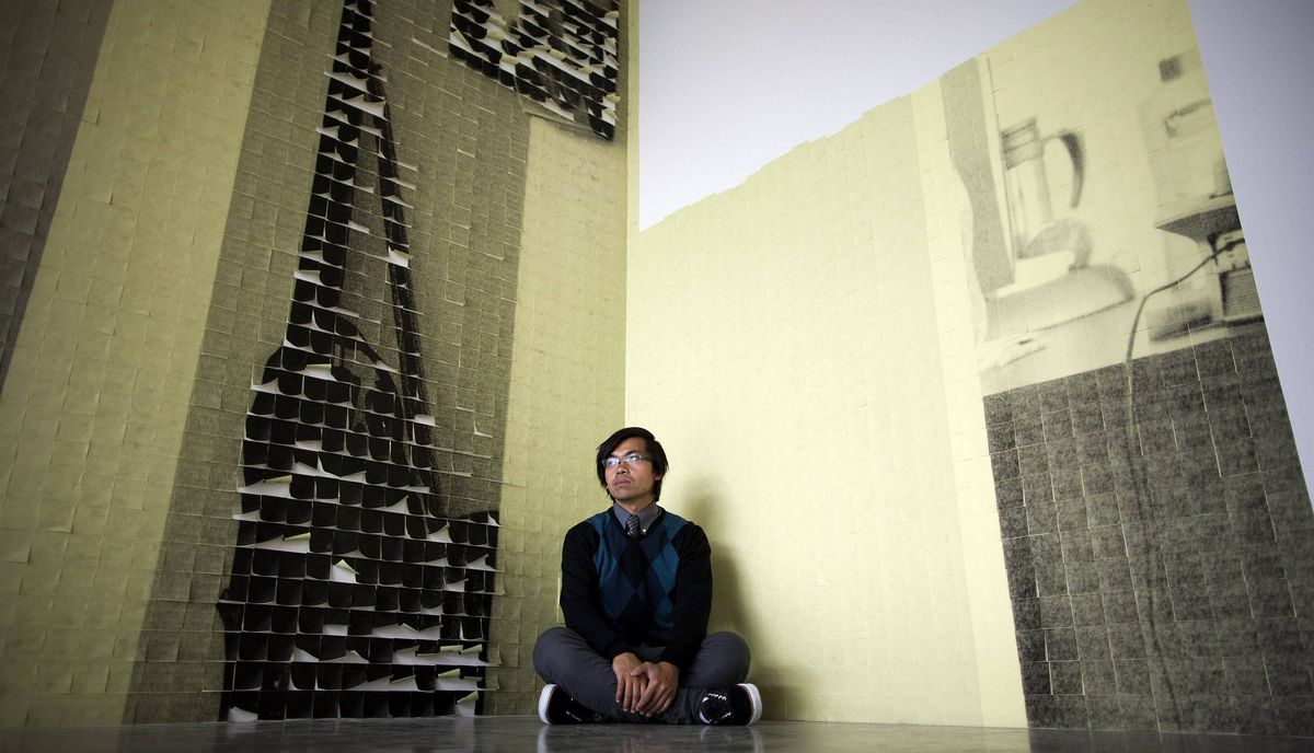 Artist Immony Men, who is creating a giant wall installation out of Post-It notes, poses with his art work at Grunt Gallery in Vancouver, British Columbia, Monday, July 25, 2011.