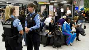 Police officers stand by as commuters wait for the reopening of the subway after smoke bombs closed the whole Montreal subway system Thursday, May 10, 2012.