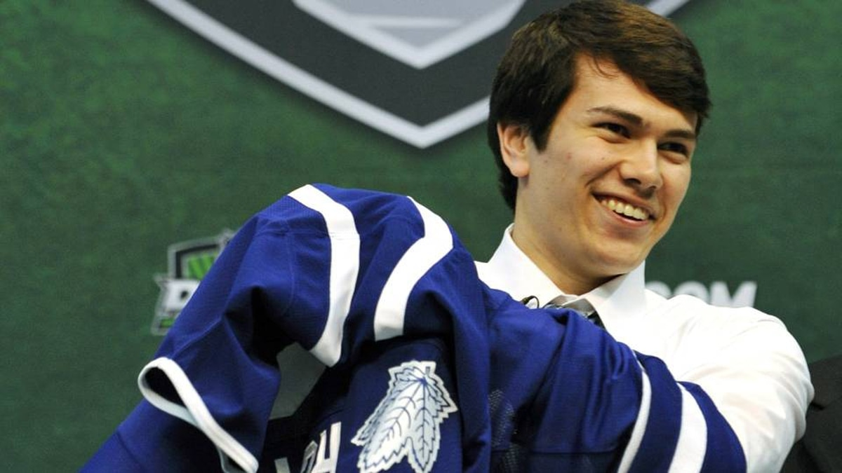 Stuart Percy puts on a jersey after being drafted in the first round by the Toronto Maple Leafs in the National Hockey League entry draft, Friday, June 24, 2011, in St. Paul, Minn.