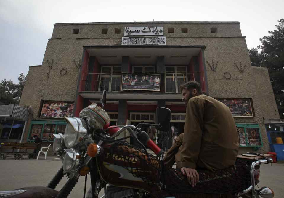 A man sits on a motorbike outside Cinema Park in Kabul. Once a treasured luxury for the elite, Afghan cinemas are dilapidated and reflect an industry on the brink of collapse from conflict and financial neglect.