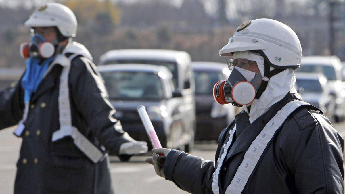 Police officers wearing respirators guide people to evacuate away from the Fukushima Daiichi nuclear plant following an evacuation order for residents who live in within a 10-km radius from the plant after an explosion in Tomioka Town in Fukushima Prefecture March 12, 2011.