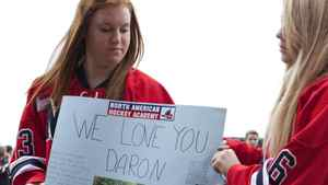 Alison Greene (left) and Brigite Baker (right) hold up a sign in memory of their former teammate Daron Richardson prior to a memorial service at ScotiaBank Place in Ottawa on Wednesday, November 17, 2010. Richardson, the 14-year-old daughter of Ottawa Senator's assistant coach Luke Richardson, died last week.