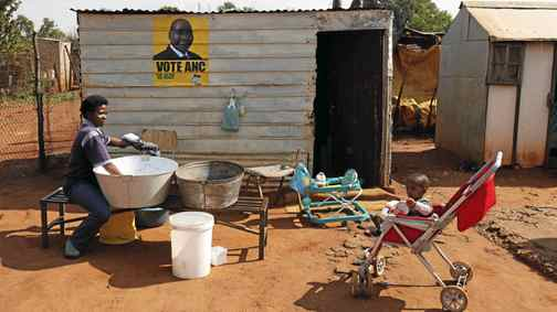 A mother washes clothes as an African National Congress (ANC) election poster is seen on the shack she and her family live in at Waterworks, an informal settlement outside Soweto May 9, 2011.