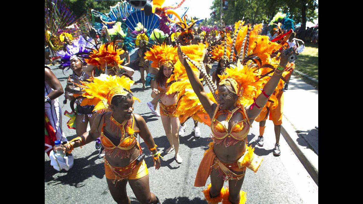 Brightly coloured dancers take part in the Caribbean Carnival parade.