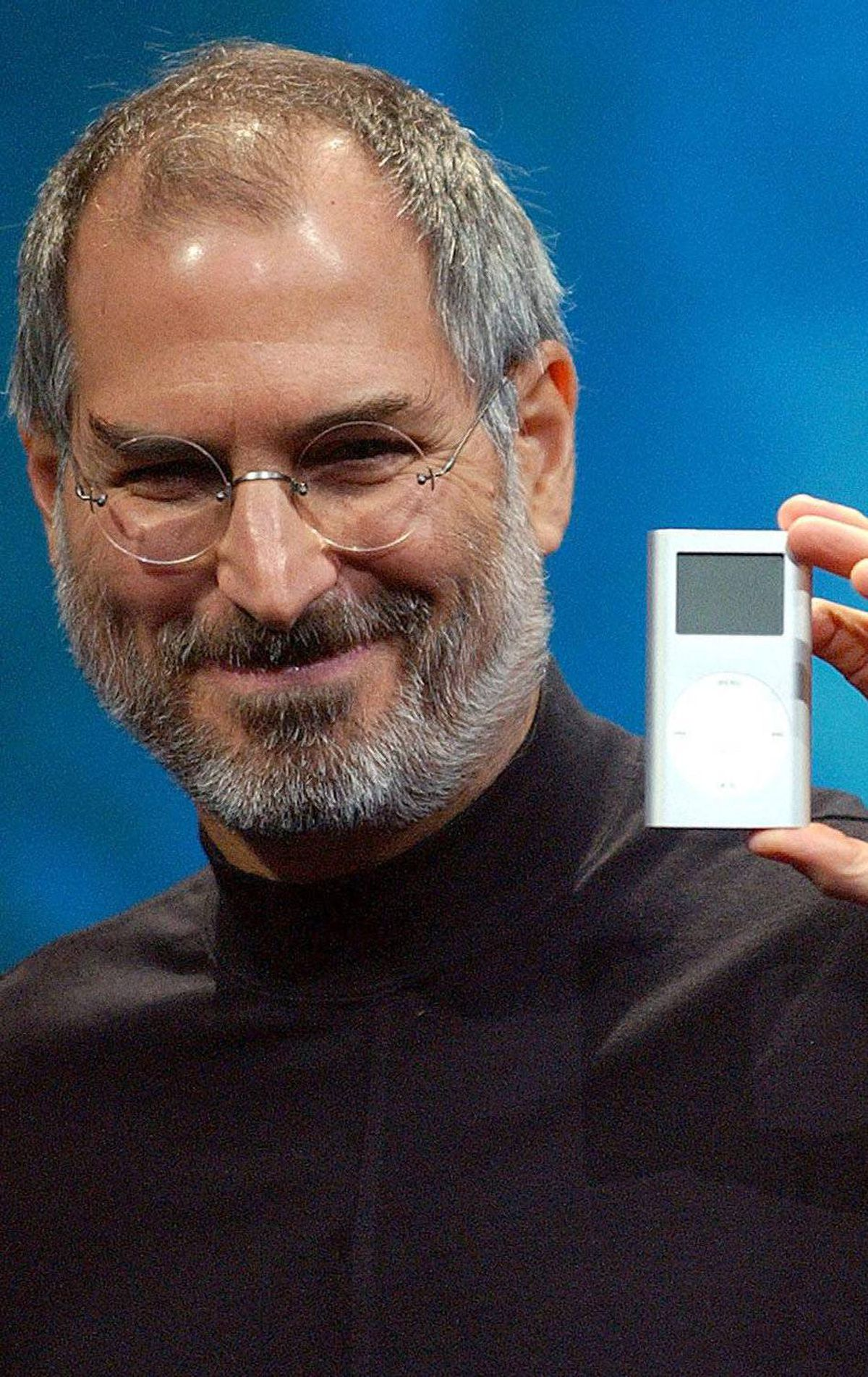 Apple CEO Steve Jobs displays his company's new product, the Mini-Ipod, at the Macworld Conference and Expo in San Francisco, Tuesday, Jan. 6, 2004. (AP Photo/Marcio Jose Sanchez)