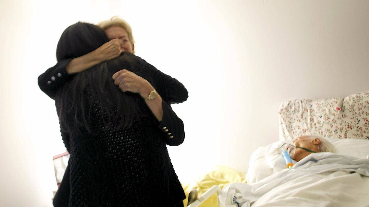 Basia Hoffman (facing the camera) hugs social worker Maxxine Rattner during a visit with her 90-year-old mother, Andrée Hoffman, who spent her final days at Kensington Hospice, a 10-bed palliative care facility that opened last summer in Toronto.