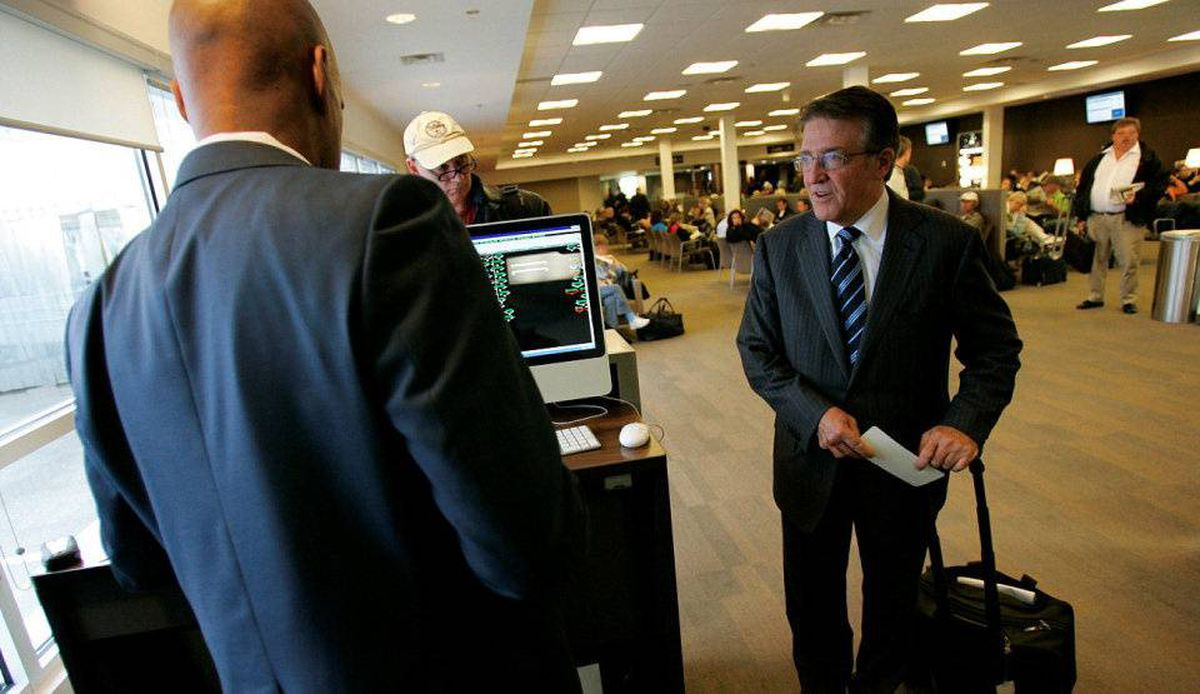 Robert Deluce, president of Porter Airlines, right, checks in with gate staff while boarding a flight in Toronto