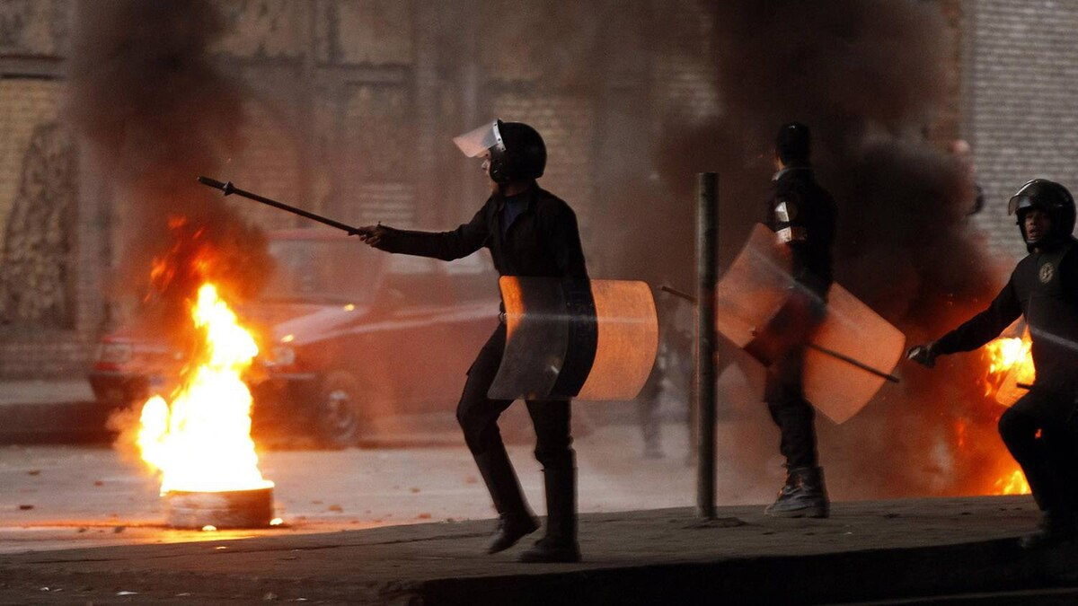 Riot police walk past a burning barricade during clashes in Cairo January 26, 2011. Thousands of Egyptians defied a ban on protests by returning to Egypt's streets on Wednesday and calling for President Hosni Mubarak to leave office, and some scuffled with police.