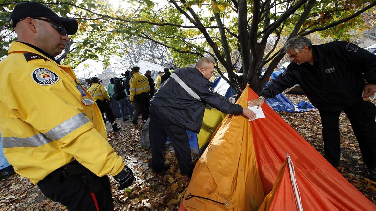 City of Toronto by-law officers are escorted by Toronto Police as they post eviction and trespass notices in the Occupy Toronto camp at St. James Park on Nov. 15, 2011.