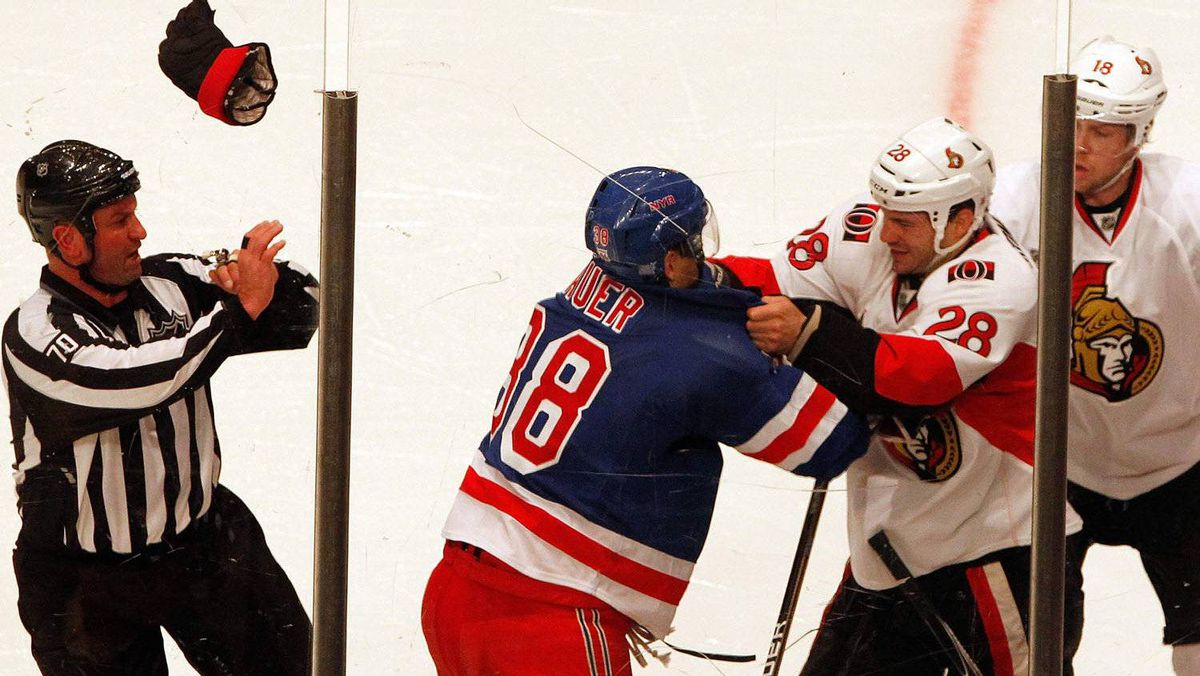 A referee dodges a glove as (L-R) New York Rangers Michael Sauer and Ottawa Senators Zenon Konopka fight during the second period of their NHL hockey game at Madison Square Garden in New York, October 29, 2011. The Sens rallied to win 5-4 in a shootout. REUTERS/Jessica Rinaldi