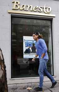 A man walks past a branch of Spain's Banesto bank in Madrid October 27, 2011.