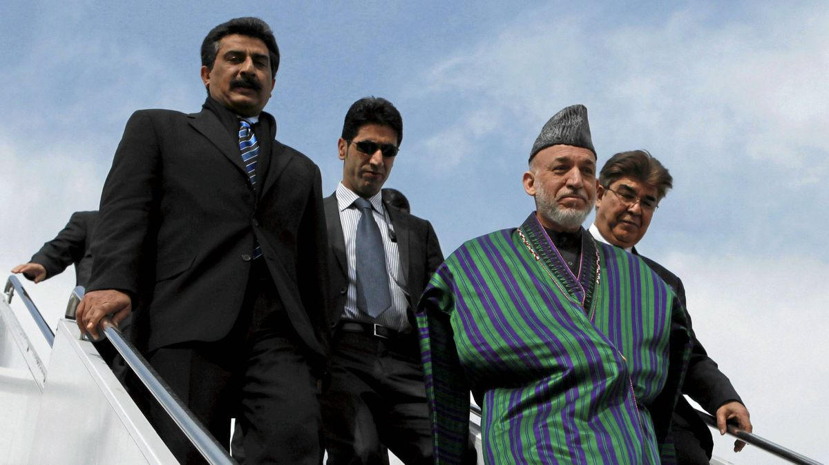 Afghanistan's President Hamid Karzai is escorted by Afghan officials as he walks down from his plane at a military base in Rawalpindi Feb. 16, 2012.