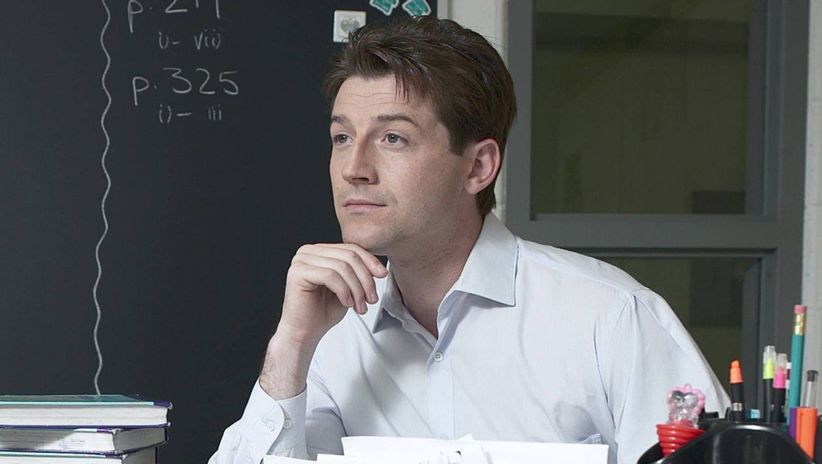 Young teacher sits thinking at a desk.
